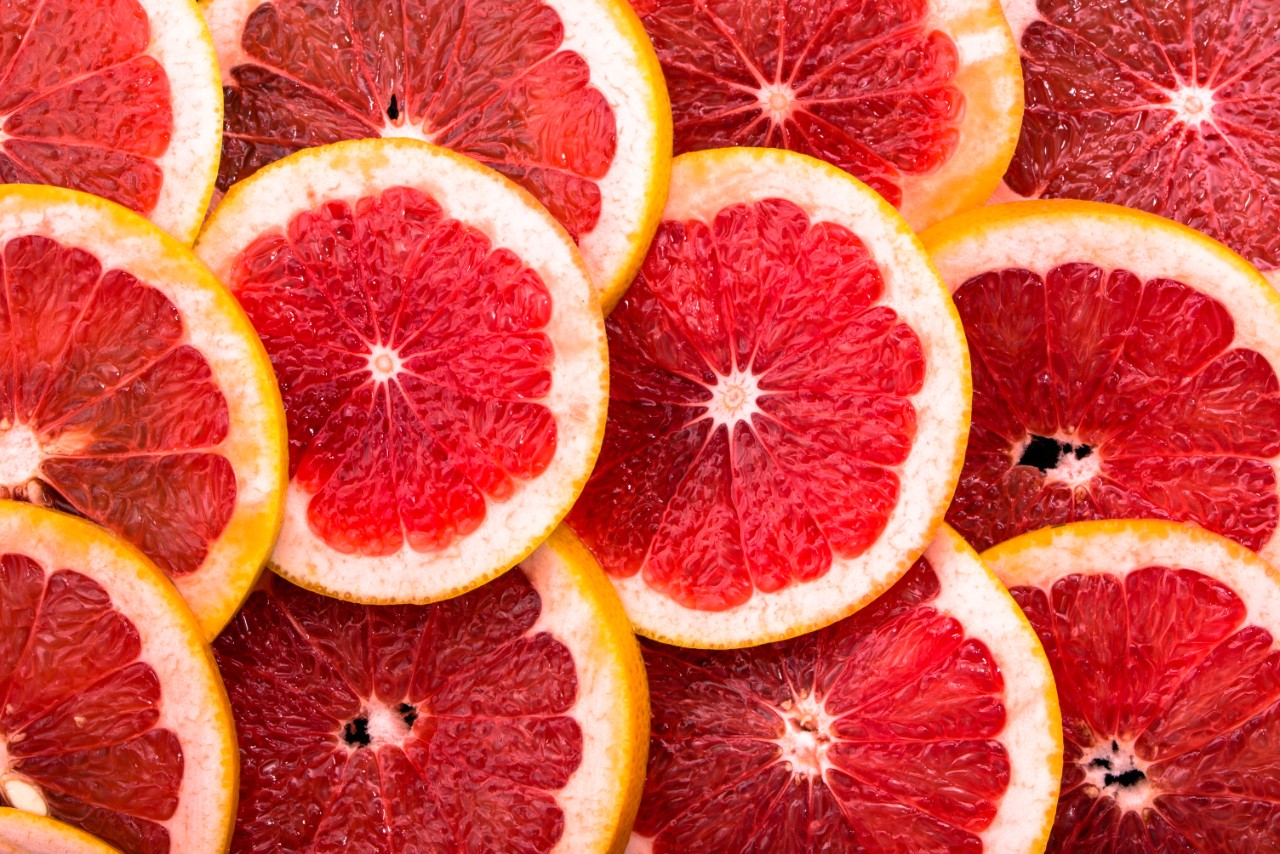 Sliced grapefruits, background, natural texture of citrus, top view, close-up
